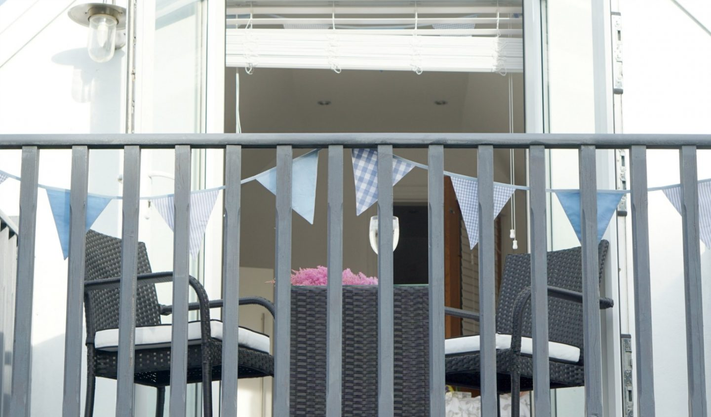 A grey painted balcony with rattan direct furniture www.extraordinarychaos.com