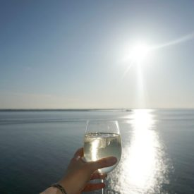 Glass of wine on balcony of Junior Suite on the Norwegian Bliss www.extraordinarychoas.com