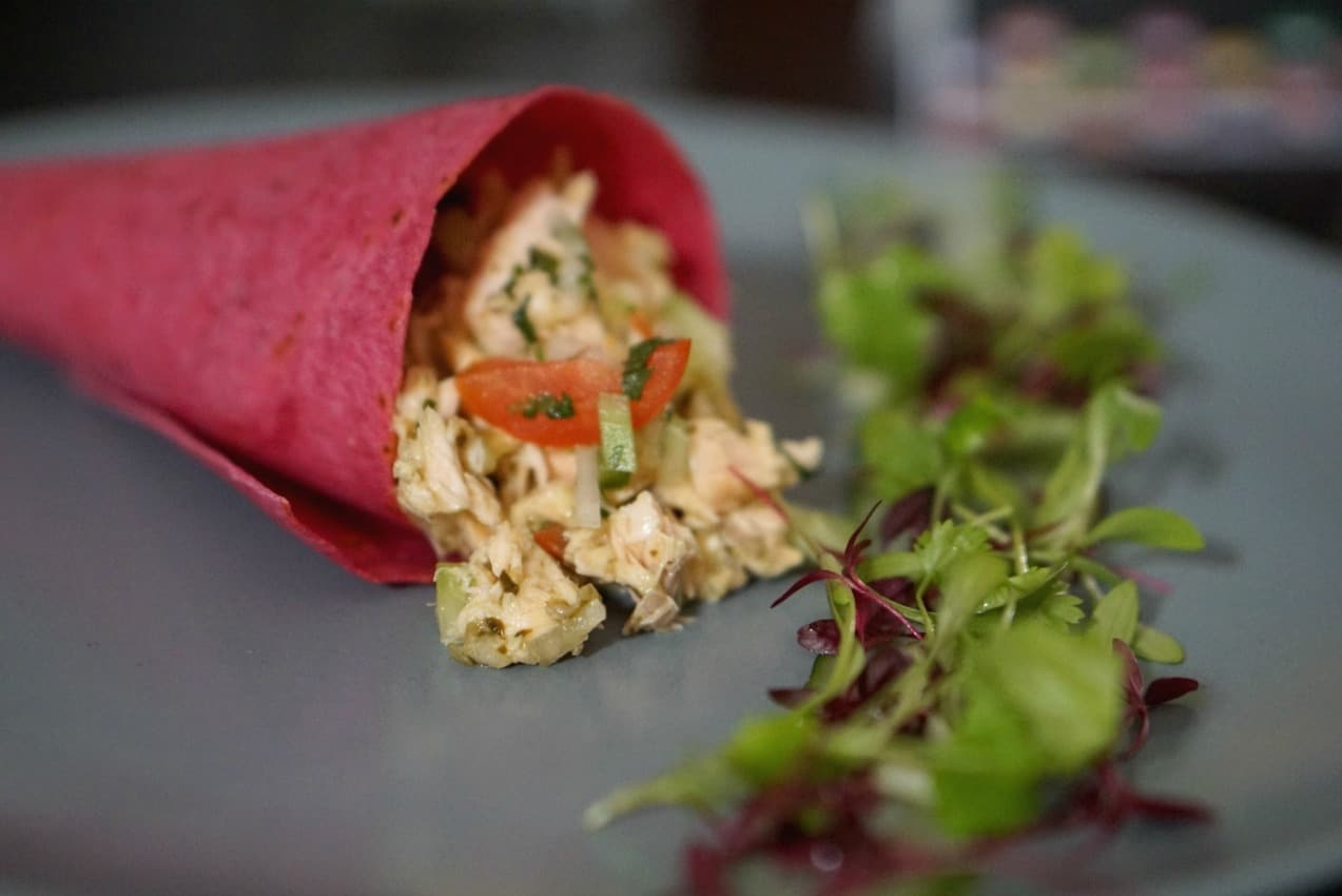Breakfast wrap filled with a citrus cucumber and tomato relish, beetroot wraps and The Saucy Fish Co.Steamed Salmon with Lime & Coriander Dressing.