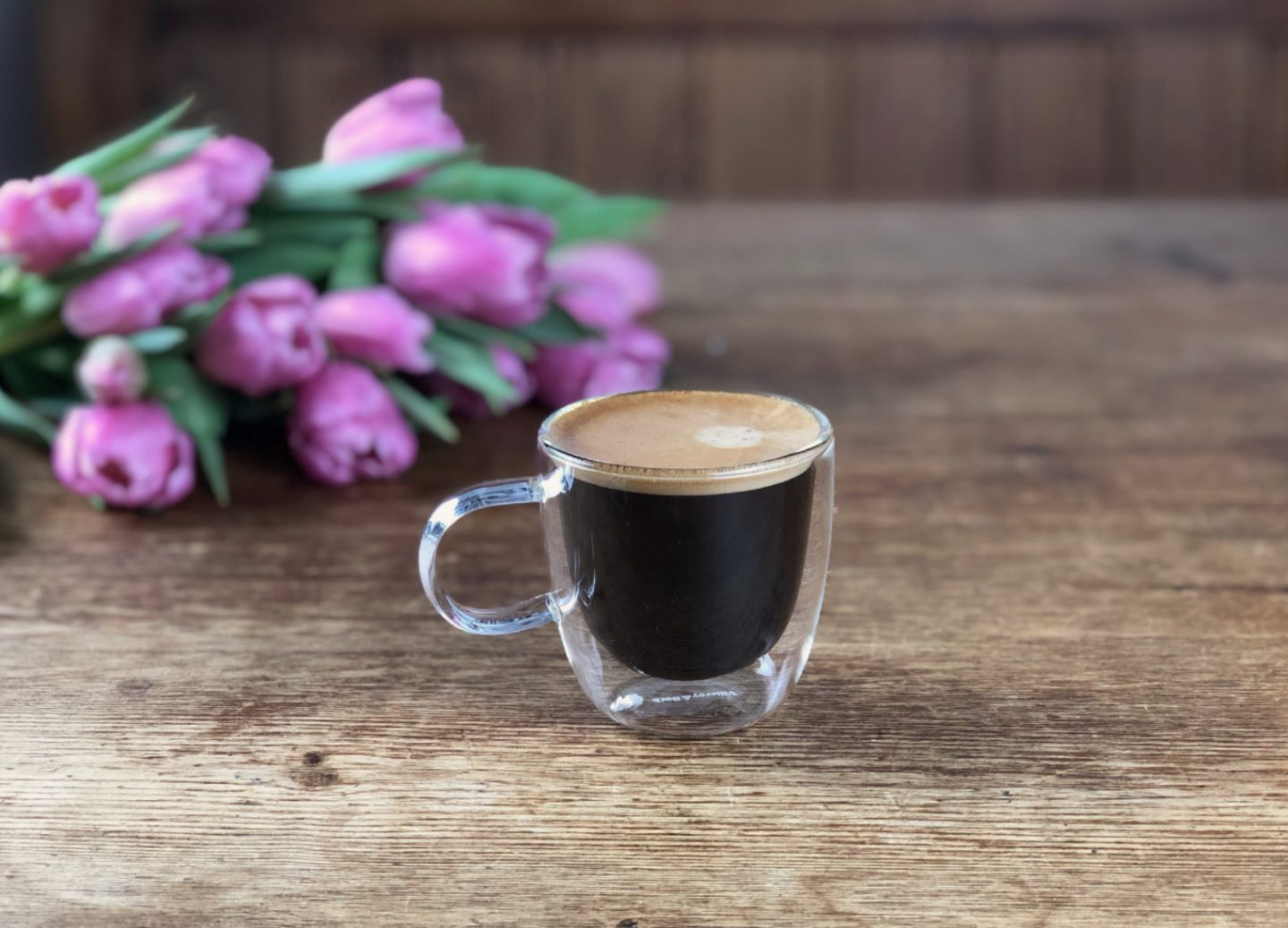 Coffee and flowers on a rustic table