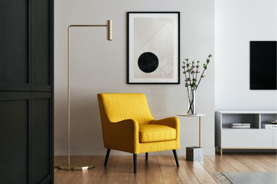 A metallic lamp behind a yellow chair in a living room