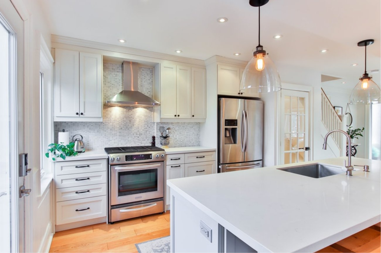 A white kitchen with lights above an island worktop