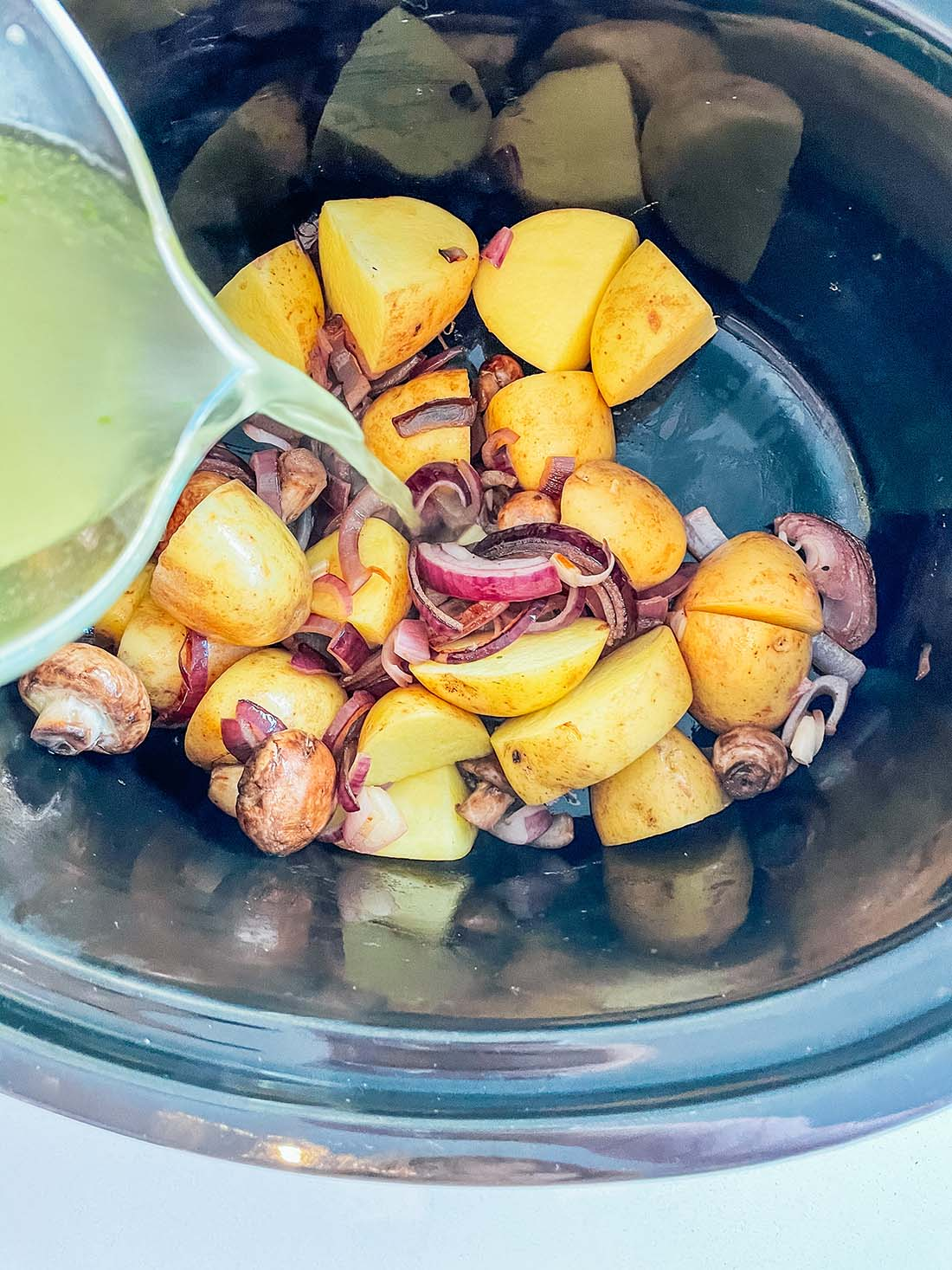 Add the potatoes and stock to the slowcooker, before adding the fried onion and mushrooms